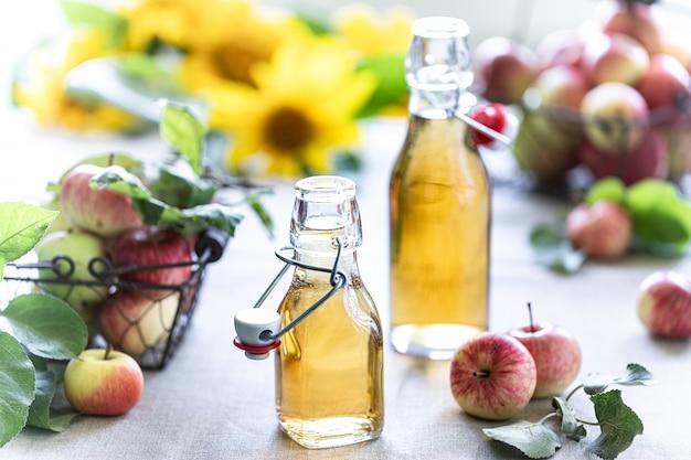 りんご酢。アップル有機酢またはサイダー木製の背景のボトル。健康的な有機食品。 Premium写真