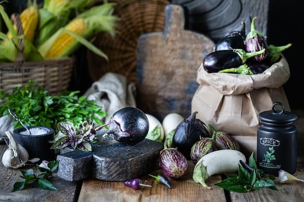 Баклажаны разных цветов и разных сортов на деревянном столе. Premium Фотографии