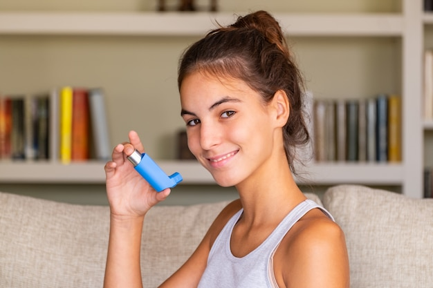 自宅のソファーに座っている吸入器を使用して若い女の子 Premium写真