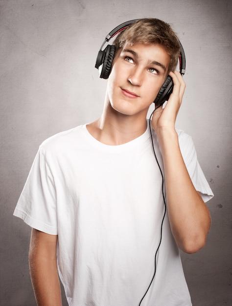 灰色の背景で音楽を聴くヘッドフォンを着ている若い男 Premium写真
