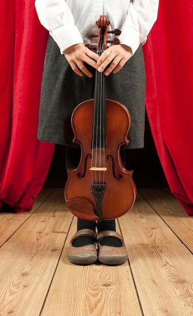 Маленькая девочка со скрипкой на сцене театра Premium Фотографии