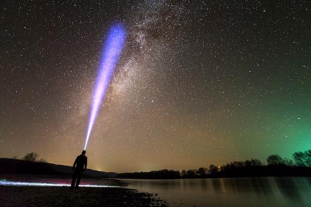 川のほとりに立っている頭の懐中電灯を持つ男の背面図 Premium写真