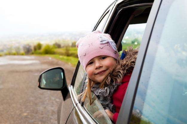 車の窓を通して見る車の中でかわいい女の子。 Premium写真