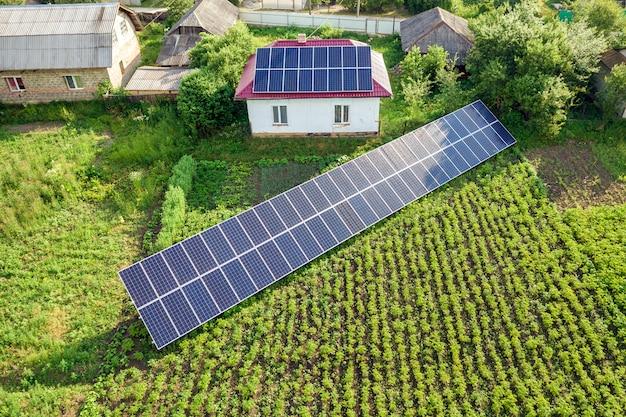 Вид с воздуха дома с голубыми панелями солнечных батарей. Premium Фотографии
