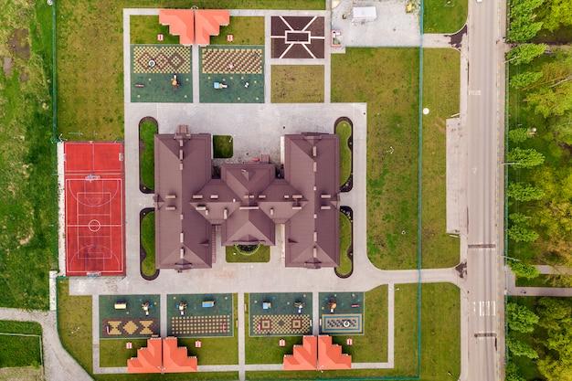 床の間と緑の芝生がある新しいプレクールの建物と庭の空中写真。 Premium写真