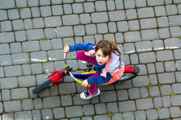 自転車に乗って長い明るい茶色の髪の少女 Premium写真