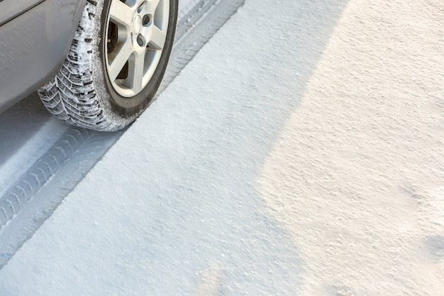 Автомобиль движется по заснеженной дороге, диски резиновые, шины в глубоком снегу транспортировка, дизайн и безопасность. Premium Фотографии