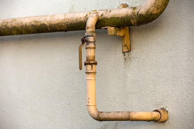 溶接継ぎ目と古い汚れた塗装黄色の天然ガス管のクローズアップの詳細 Premium写真