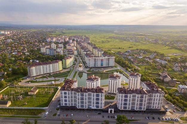 Взгляд сверху городского развивающего ландшафта города с высокорослыми жилыми домами и домами пригорода. Premium Фотографии