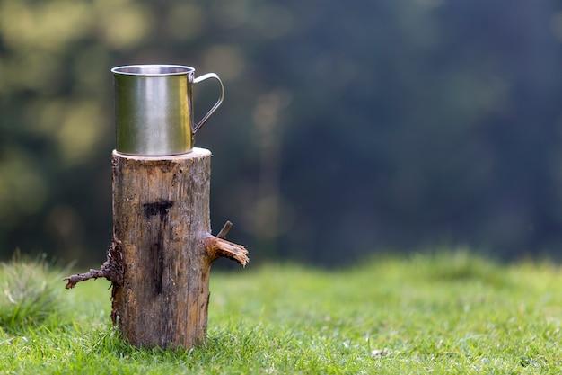 クローズアップショット、草が茂った日当たりの良い夏の森の屋外で孤立した木の切り株に大きな光沢のあるブリキのマグカップ Premium写真