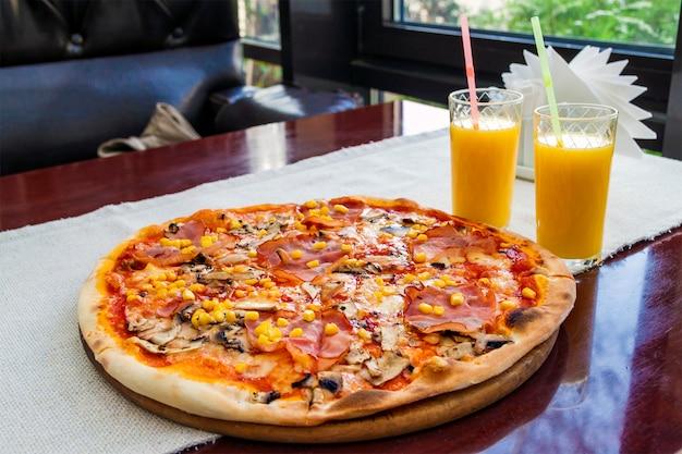 Крупным планом пиццы с мясом и кукурузой и два стакана апельсинового сока Premium Фотографии