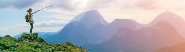 Молодая стройная блондинка туристическая девушка с рюкзаком указывает с палкой на туманную панораму горного хребта Premium Фотографии