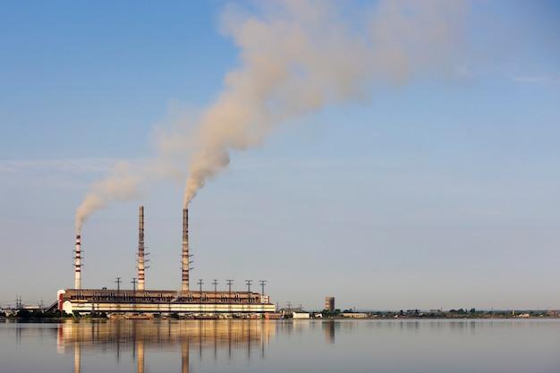 Тепловая электростанция высоких труб с густым дымом отражается на поверхности воды. загрязнение окружающей среды концепции. Premium Фотографии