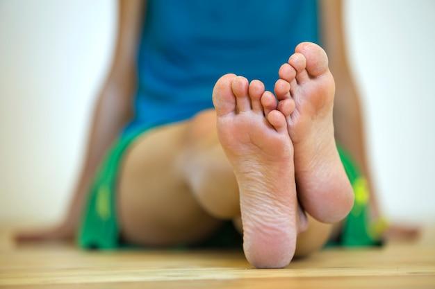 Крупным планом женщина сидит на полу с босыми ногами. уход за ногами и концепция лечения кожи. Premium Фотографии