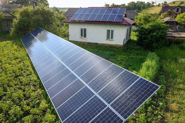 Вид с воздуха дома с голубыми панелями солнечных батарей для экологически чистой энергии. Premium Фотографии