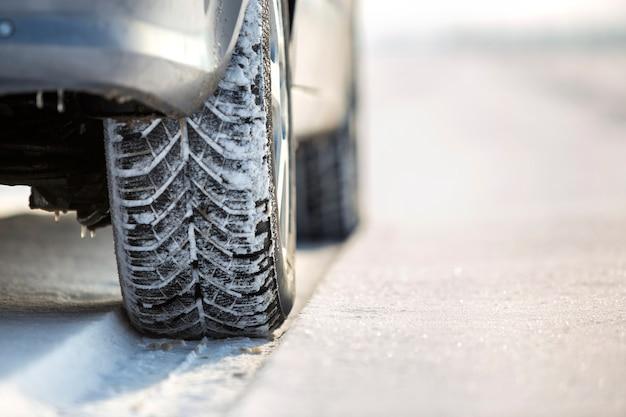 雪道で冬用タイヤの車のホイールのクローズアップ Premium写真