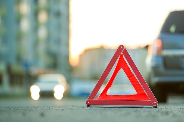 赤い緊急の三角形の一時停止の標識と街で壊れた車。 Premium写真