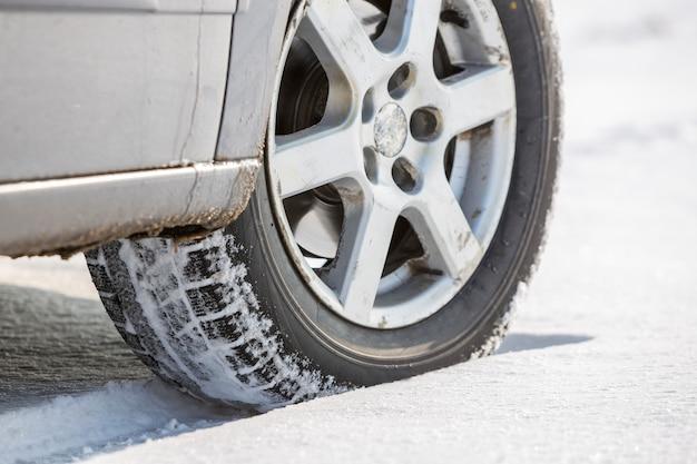 深い雪の中で車の車輪のゴム製タイヤのクローズアップ。 Premium写真