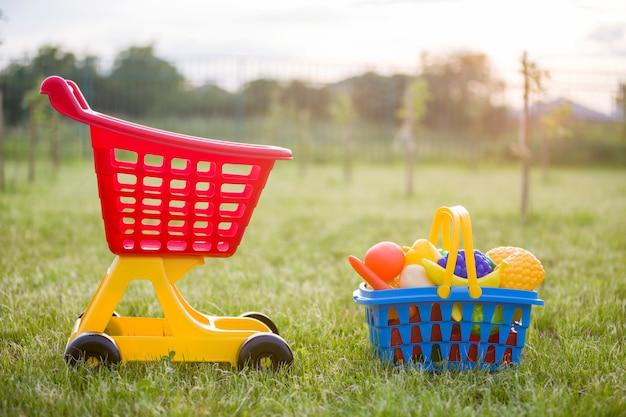 Торговая тележка и корзина с игрушечными фруктами и овощами. Premium Фотографии