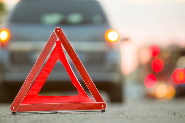 赤い緊急三角形の一時停止の標識と街で壊れた車。 Premium写真