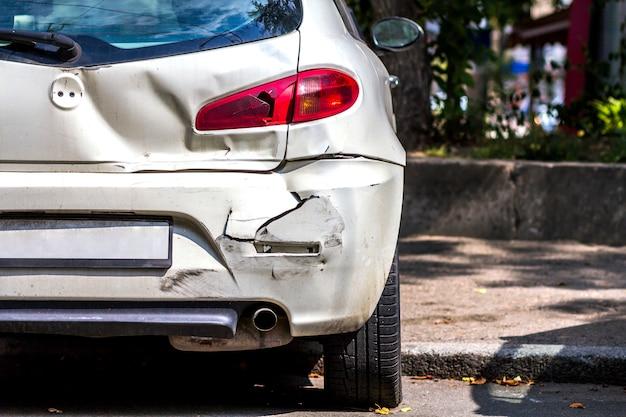 道路上の事故により破損した白い車の背面 Premium写真