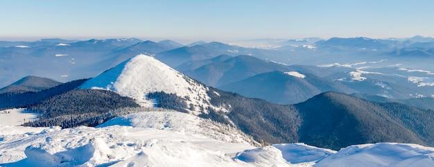 冬の山の風景のパノラマ。白い雪に覆われた山の丘 Premium写真