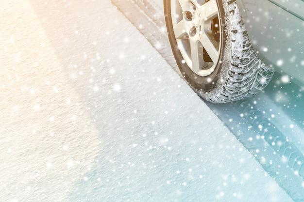 深い冬の雪道で車の車輪のゴム製タイヤのクローズアップ Premium写真