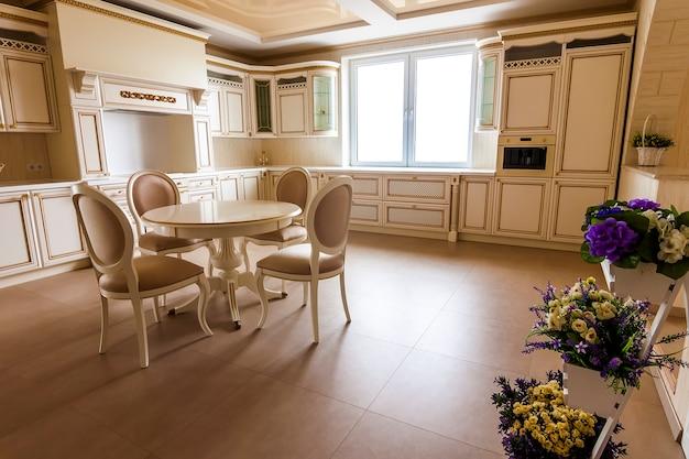 豪華なモダンなキッチンインテリア。ベージュのキャビネットを備えた豪華な家のキッチン Premium写真