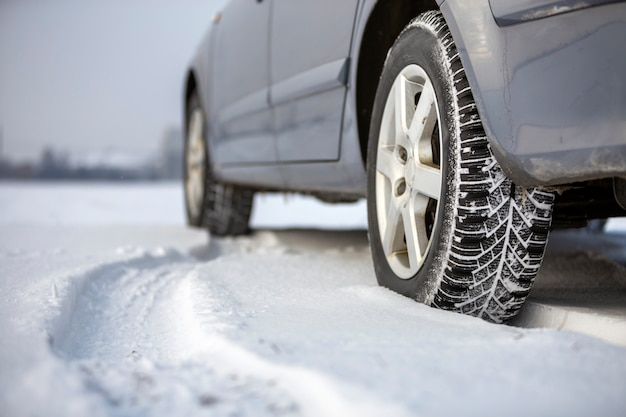 冬の日に雪道に駐車して車のタイヤのクローズアップ。輸送および安全コンセプト。 Premium写真