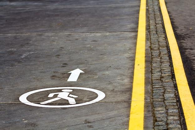 アスファルト路面の道の標識を歩く Premium写真