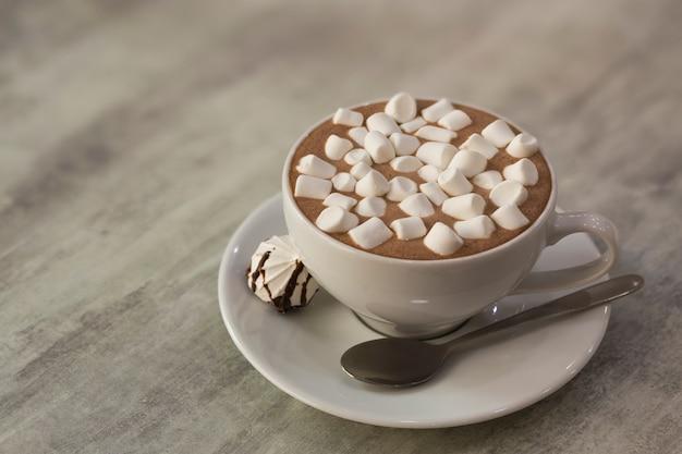 明るい背景に磁器プレートにマシュマロとコーヒーのマグカップ Premium写真