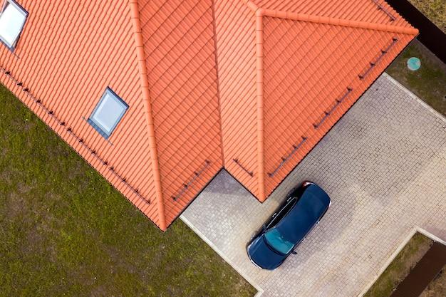 屋根裏部屋の窓と舗装された庭の黒い車の家の空撮 Premium写真