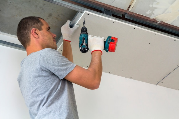 建設労働者は、乾式壁で吊り天井を組み立て、ドライバーで乾式壁を天井の金属フレームに固定します。 Premium写真