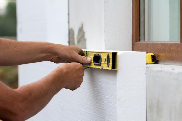 レベルとナイフで白い硬質ポリウレタンフォームシートを測定および切断の労働者の手 Premium写真