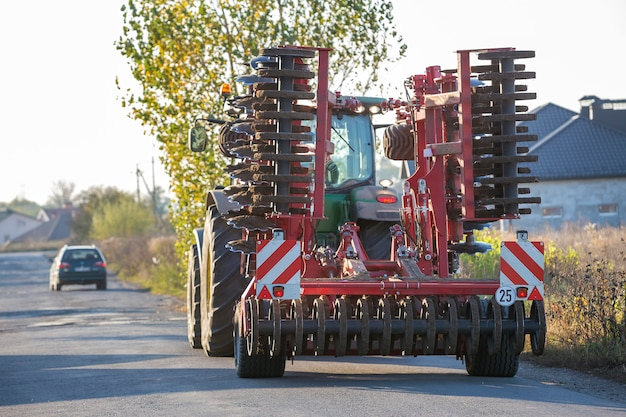 トラクターは、晴れた日に田舎道に沿って運転するディスクハローと組み合わされます。 Premium写真