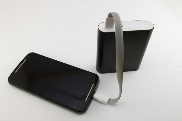 白で隔離されるブラックパワーバンクから充電するスマートフォン。スマートフォンとパワーバンクのコンセプト。 Premium写真