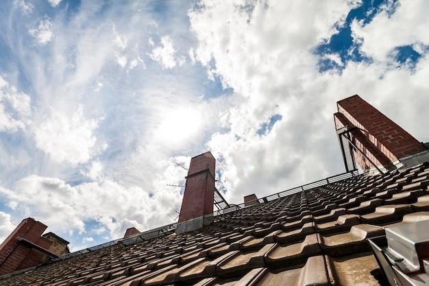 暗いオレンジ色のレンガと白い雲と劇的な青い空を背景に黄色の煙突の瓦屋根 Premium写真