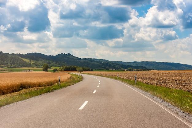 緑の野原と夏の日の青い空に雲を介してドイツのアスファルト田舎道 Premium写真