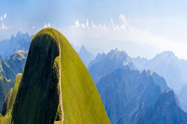 Панорама зеленых холмов в летних горах с гравийной дорогой для путешествий на машине Premium Фотографии