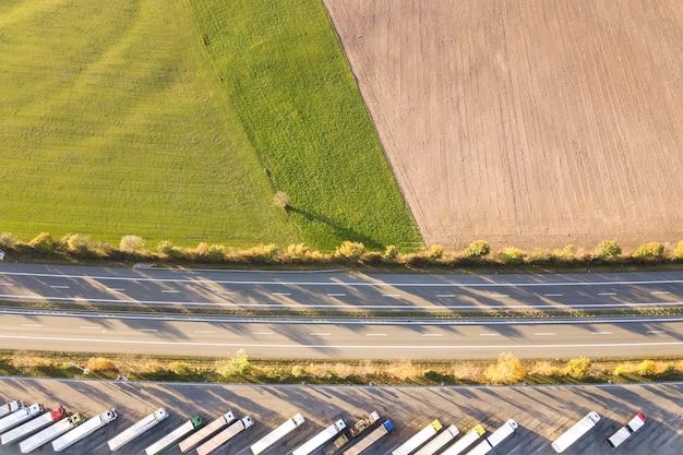 Сверху вниз вид с шоссе автомагистрали между штатами с быстрым движением трафика и стоянки с припаркованными грузовиками. Premium Фотографии