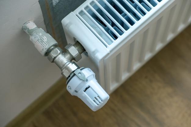内壁の金属製ラジエーターの快適な温度調節のためのラジエーターバルブの加熱のクローズアップ。 Premium写真