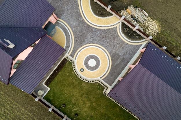 Воздушный взгляд сверху крыши гонт дома на предпосылке зеленой лужайки и красочного вымощенного двора с геометрической абстрактной картиной. кровельные, ремонтные и ремонтные работы. Premium Фотографии