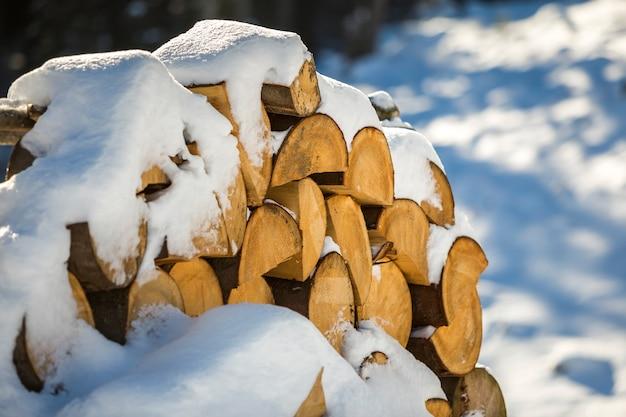 Аккуратно сложенный стек измельченных сухих стволов древесины покрыты снегом на открытом воздухе на яркий холодный зимний солнечный день, абстрактный фон, дрова журналы, подготовленные к зиме, готовы к сжиганию. Premium Фотографии