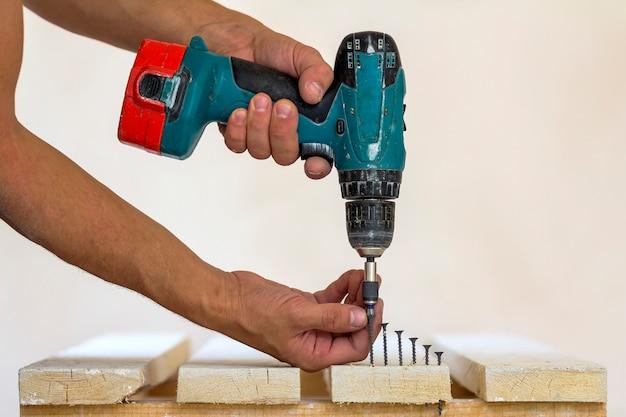 Рука рабочего ввинчивает винт в деревянную доску с аккумуляторной отверткой. человек плотник на ручной работе Premium Фотографии