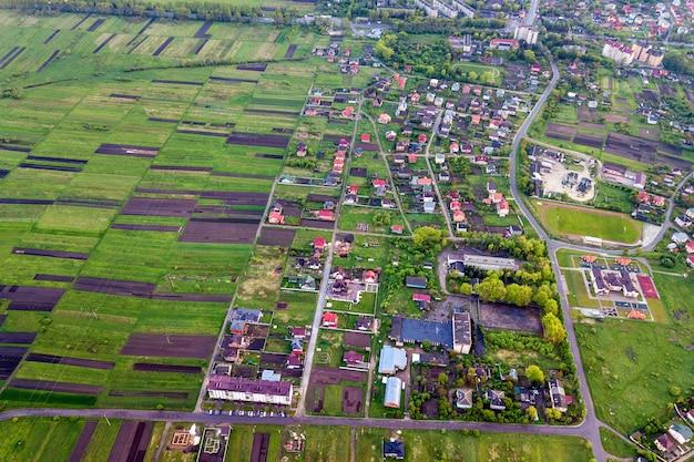 春または夏の日の田園風景。日当たりの良い夜明けの緑と耕した畑、村や町の家の屋根と道路の空撮。ドローン写真。 Premium写真
