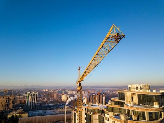 Квартира или офис высотного здания в стадии строительства, вид сверху. кран башни на ярком голубом небе копирует предпосылку космоса, ландшафт города протягивая к горизонту. дрон аэрофотосъемки. Premium Фотографии
