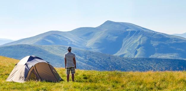カルパティア山脈のキャンプテントの近くに立っているハイカーの男。観光客は山の景色を楽しみます。旅行のコンセプト。 Premium写真