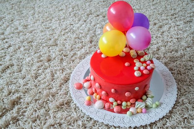 空気風船と自家製の赤い誕生日ケーキ Premium写真
