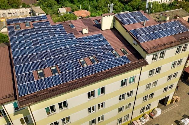 産業用建物の屋根に取り付けられた多くのソーラーパネルの空撮。 Premium写真