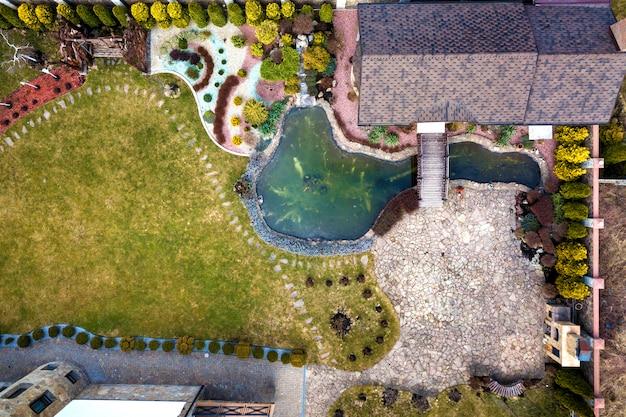 美しく手入れされた施設の空撮。レクリエーション家のコテージの屋根、明るい晴れた日に生態地域の池。近代建築、造園のコンセプト。 Premium写真